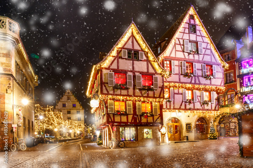 Staande foto Zwart Traditional Alsatian half-timbered houses in old town of Colmar, decorated and illuminated at snowy christmas night, Alsace, France