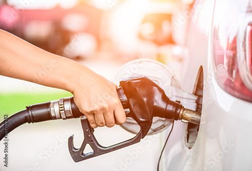 Fotografía Closeup of woman  hand holding a fuel pump at a station.