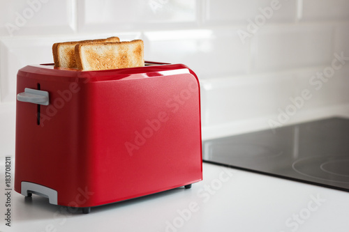 Red toaster with toasted bread for breakfast inside. White background. White kitchen table.