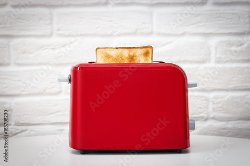 Red toaster with toasted bread for breakfast inside. White table. White brick wall.
