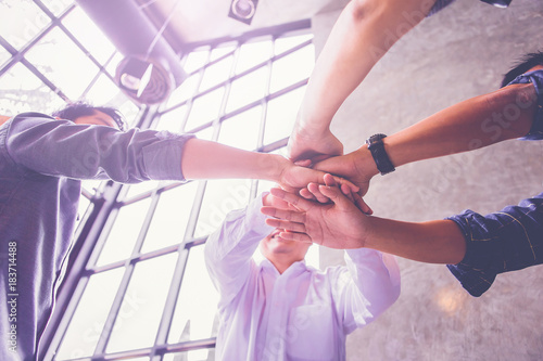 Stampa su Tela  Team work concept. Business people joining hands. Low angle view