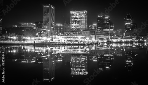 Fotografering  Baltimore  skyline and docks reflecting in the water at night