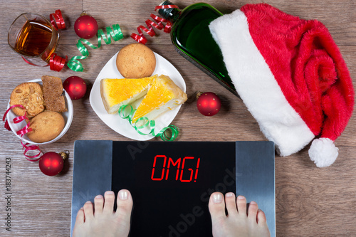 "Fotografía  Female feet on digital scales with sign ""omg!"" surrounded by Christmas decorations, bottle, glass of alcohol and sweets"