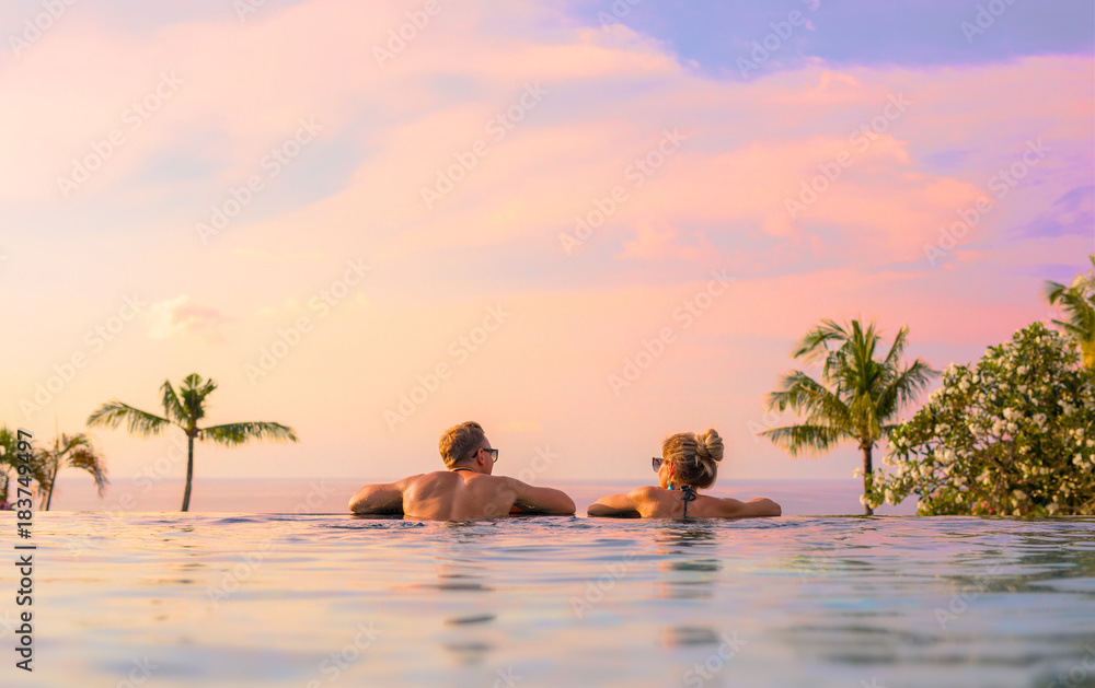Fototapety, obrazy: Romantic couple looking at beautiful sunset in luxury infinity pool