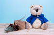 Baby birthday theme with teddy bear and gift box on a blue background