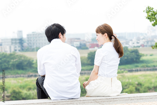 Fotografiet  屋外で座って会話するカップル