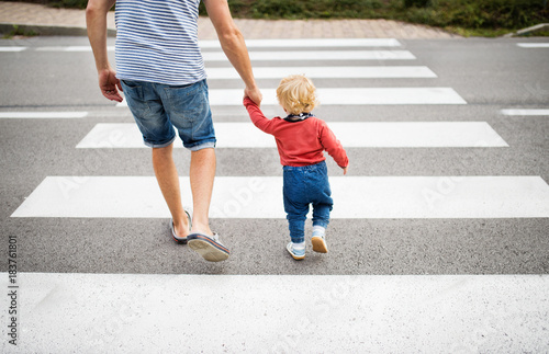 Foto Father with little boy crossing the road on crosswalk.