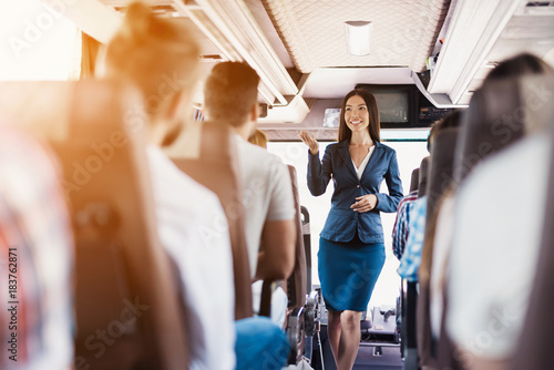 Poster Avion à Moteur A stewardess is posing on the bus. It stands between the rows of seats on which passengers are sitting.
