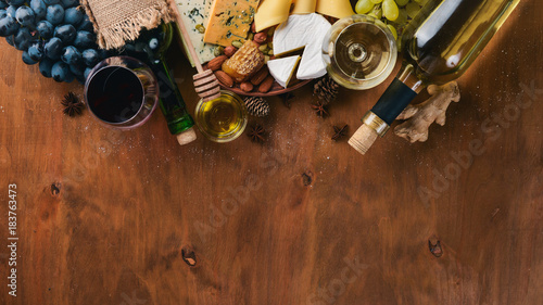 Fototapeta A bottle of wine, and a large assortment of cheeses, honey, nuts and spices, on a wooden table. Top view. Free space for text. obraz na płótnie