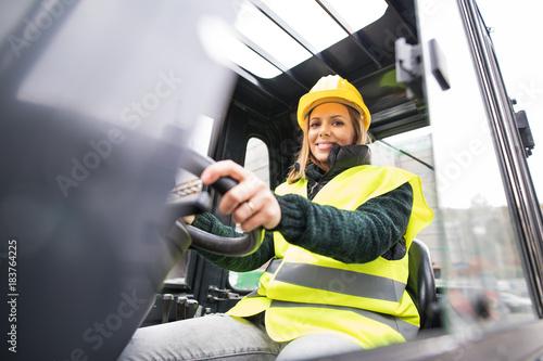 Obraz Woman forklift truck driver in an industrial area. - fototapety do salonu