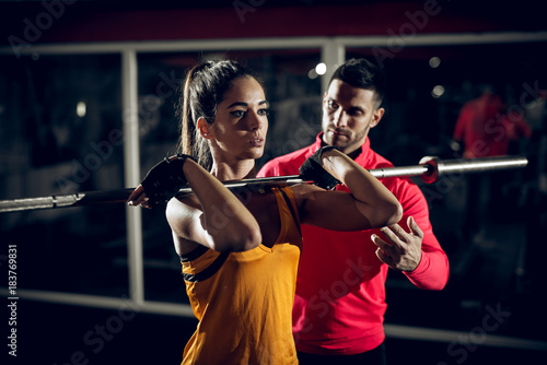 Close up motivated focused attractive young fitness woman doing squad exercise with a bar in front on the shoulders in the gym while her personal trainer standing next to her.