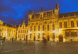 BRUGES, BELGIUM - MARCH 2015: Tourists visit ancient medieval Burg Square at night. Brugge attracts more than 2 million people annually
