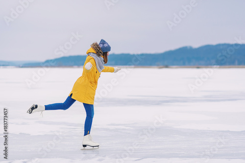 Fotografie, Obraz Young beautiful girl in yellow jacket is skating at winter on a frozen lake
