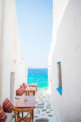 Fototapeta Do restauracji Benches with pillows in a typical greek outdoor cafe in Mykonos with amazing sea view on Cyclades islands