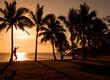 Slackliner im Sonnenuntergang am Strand Grande Anse auf der französischen Überseeinsel La Réunion im Indischen Ozean
