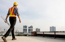 Professional Foreman Wearing Safety Helmet Hold Blueprint While Walking On The Building Deck