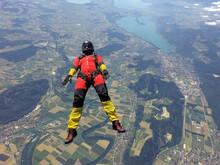 Female Skydiver Free Falling On Back Above Landscape