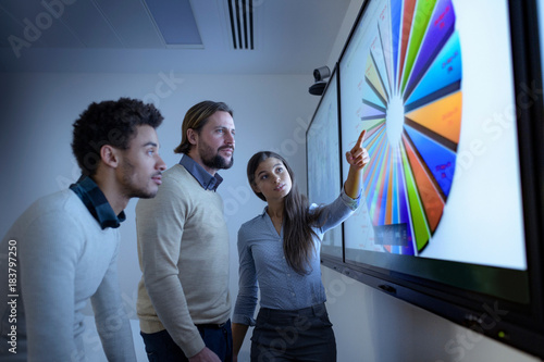 Teacher and apprentices studying graphical screen display in railway engineering facility