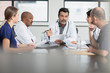 Group of doctors sitting at table, having discussion