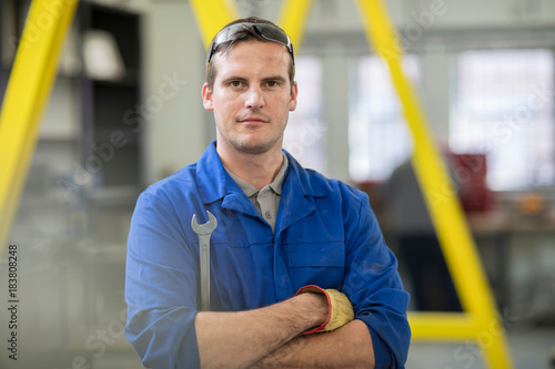 Portrait of male car mechanic with wrench in repair garage