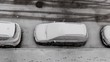 The first snowfall, the onset of winter. The yard and the car are covered with snow. View from above.