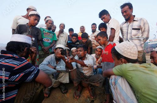 Rohingya refugees watch a news video clip on a mobile phone at