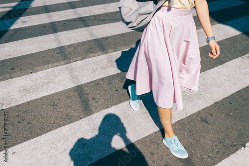 Fototapeta Young woman in a pink skirt and sneakers
