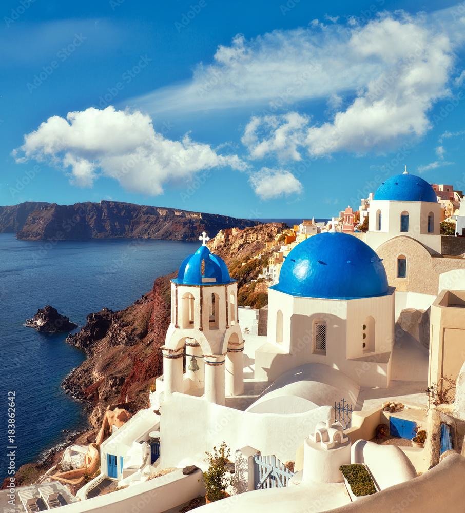 Fototapeta Local church with blue cupola in Oia village in Santorini, panoramic image