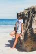 Beautiful young woman in sunglasses posing on the beach of a tropical island of Bali.