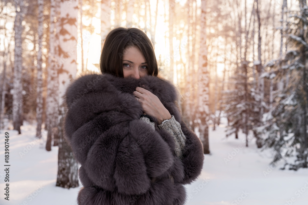 Fototapeta Girl in a fur coat against a background of snow-covered trees