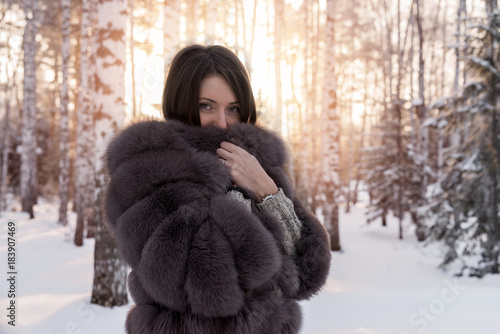 Cuadros en Lienzo Girl in a fur coat against a background of snow-covered trees