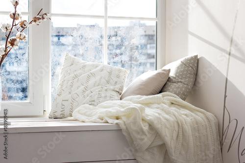 Valokuvatapetti cushions and a knitted plaid on the windowsill.