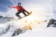 Snowboarder springt durch die Luft ins Sonnenlicht