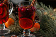 Mulled wine. Christmas hot drink with citrus, apple and spices in a glass cup on a black background.