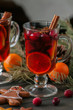 Mulled wine. Christmas hot drink with citrus, apple and spices in a glass cup and gingerbread cookies on a black background.