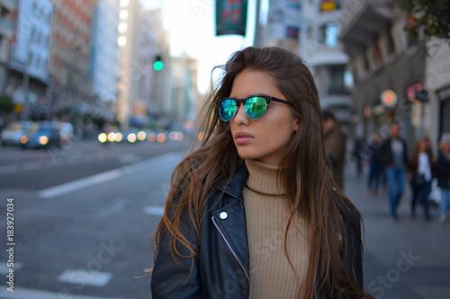 Mujer  joven estilosa  con gafas de sol y chaqueta negra caminando o realizando compras por la calle gran via de la ciudad de Madrid durante el atardecer