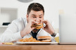 overweight businessman eating hamburger and french fries in office