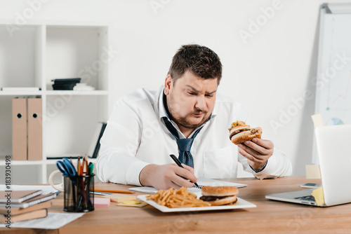 overweight businessman working while eating hamburger and french fries in office Canvas Print