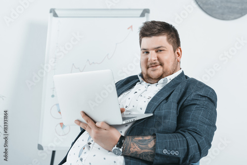 Photo overweight businessman in suit working with laptop in office