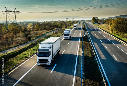 Photo Caravan of white trucks in line on country highway