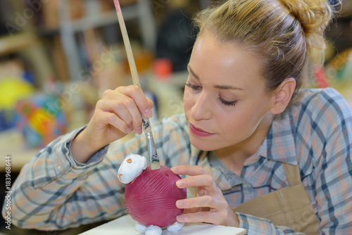 artist making and painting a clay sculpture