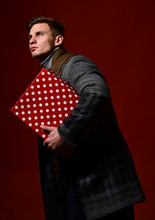 Macho Carries Present On Red Background. Guy With Serious Face