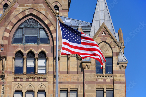 Foto op Plexiglas Texas US National Flag in front of Syracuse Savings Bank Building at Clinton Square in downtown Syracuse, York State, USA.
