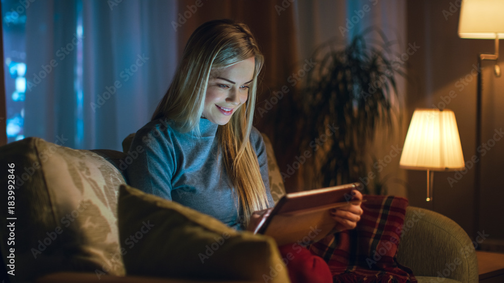 Fototapety, obrazy: Beautiful Young Woman in Her Living Room. She is Sittin on a Sofa and Uses Tablet Computer. Behind Her Big City is Seen in the Window.