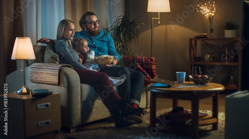 Fotomural  Long Shot of a Father, Mother and Little Girl Watching TV