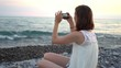 Young woman using smartphone to take photo of boat on beach
