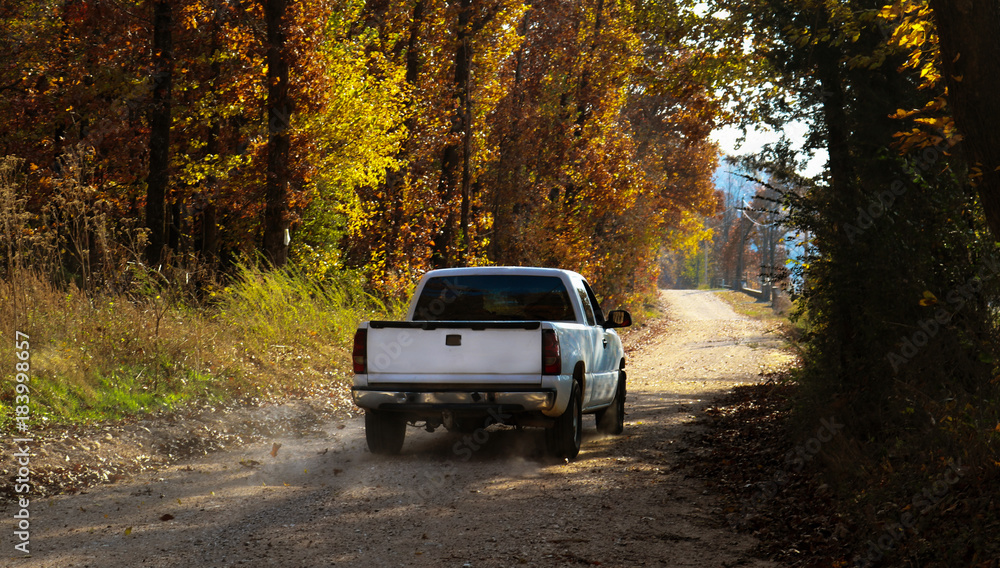 Fototapety, obrazy: White pickup truck driving down dusty dirt road with fall leaves and dust behind