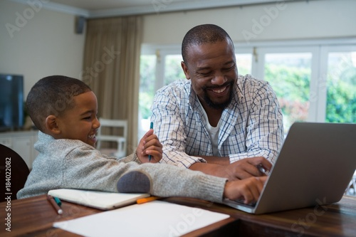 Fototapety, obrazy: Father and son using laptop in living room