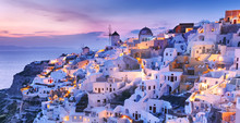 Magnificent Twilight Scenery Of Town Oia - IA Skyline On Wonderful Island Santorini In Warm Waters Of Greek Aegean Sea, Mediterranean Region. Wonderful Lights Of Night Village At The Slope Of Volcano.