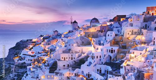 Fototapeta Magnificent twilight scenery of town Oia - IA skyline on Wonderful island Santorini in warm waters of Greek Aegean Sea, Mediterranean region. Wonderful lights of night village at the slope of volcano. obraz